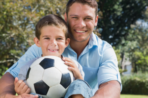 proud dad with soccer playing son