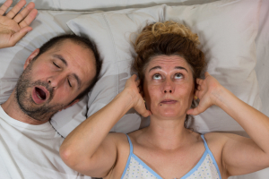 Woman covering ears due to husband snoring