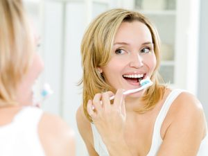 woman maintaining good oral hygeine at home.